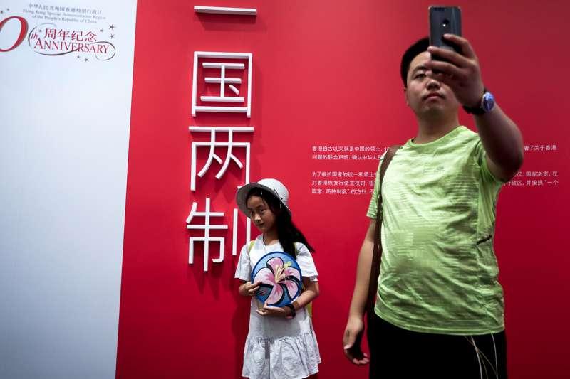 2017年7月2日,民眾在北京的一個慶祝香港回歸、實行一國兩制20週年的活動上留影。(美聯社)