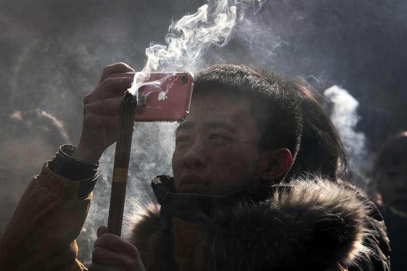 一名中國男子拿著iPhone拍照。蘋果公司以中國智慧型手機銷售趨緩為由,逾15年來首度下修單季營收預測。(AP)