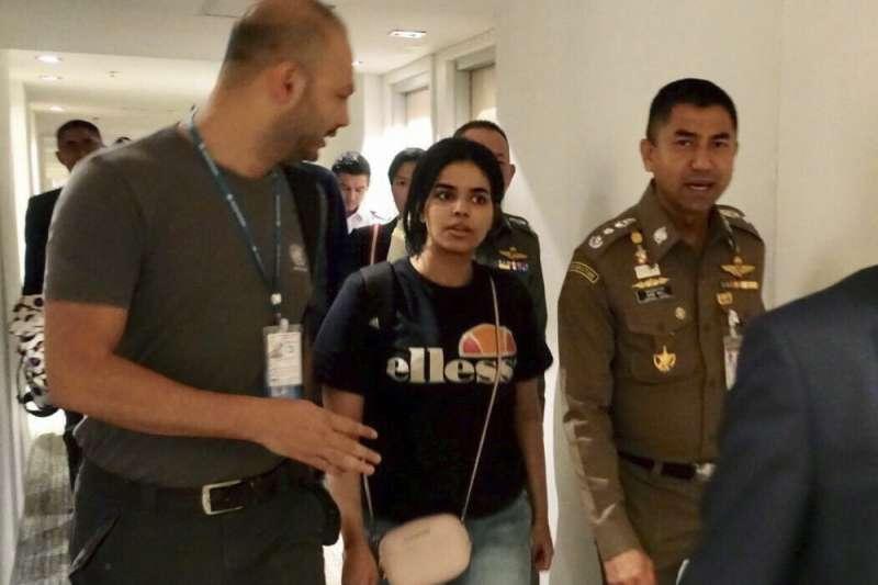 沙烏地阿拉伯18歲少女奎農(中)在泰國移民署警長蘇拉察特(右)及聯合國難民署官員的陪同下,離開機場過境旅館(美聯社)