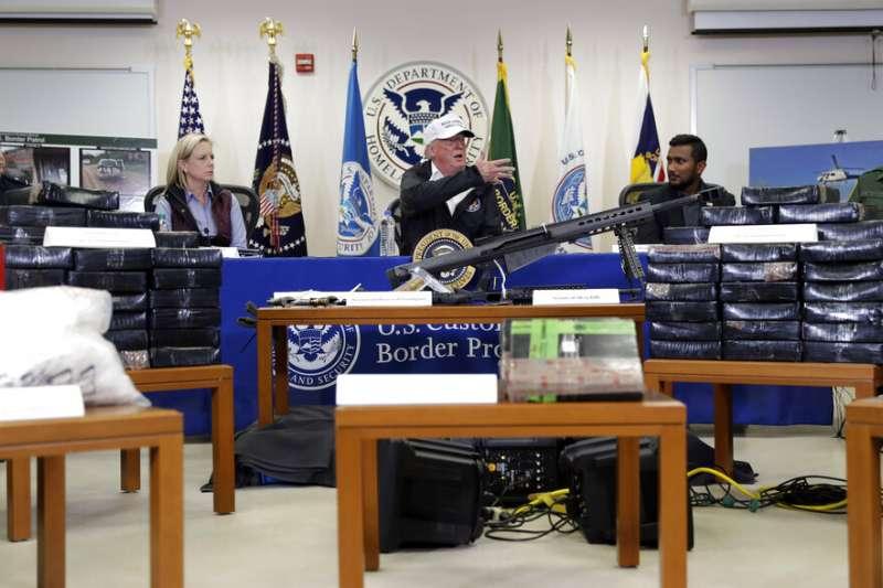 川普在麥卡倫市(McAllen)聽取邊境官員簡報,官員們也展示了收繳的毒品與槍枝。(美聯社)