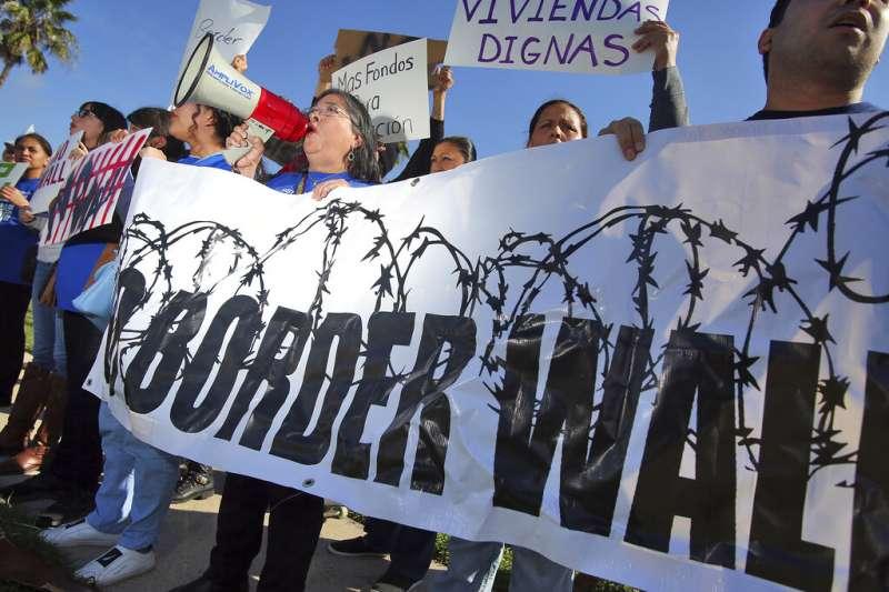 川普到德州視察美墨邊境,反對蓋牆的民眾舉布條抗議。(AP)