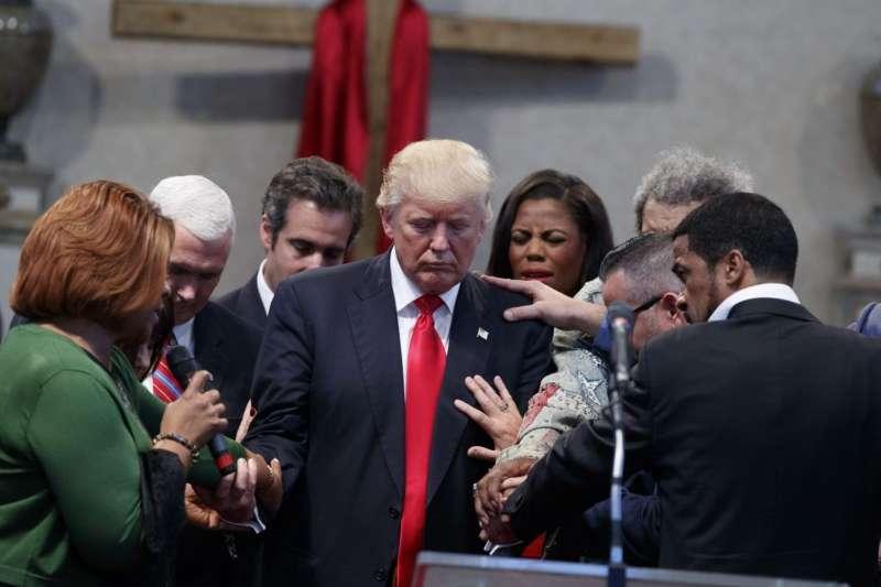 俄亥俄州基督教教會「克里夫蘭高地新靈復興中心」的成員為川普禱告。(美聯社)