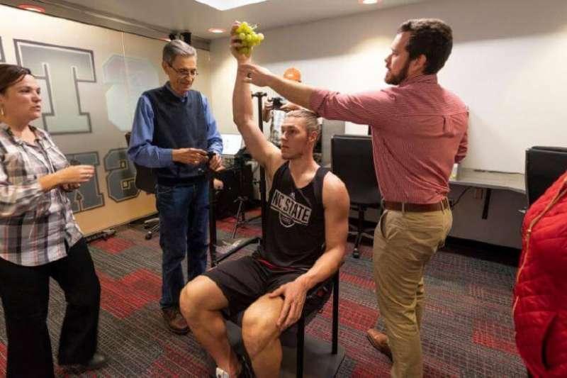 此圖為Walker在位於羅里(Raleigh)的球隊籃球中心練習場模擬拿著葡萄的姿態,修復團隊們從旁協助Walker將手臂的位置調整成符合Bacchus雕像的樣子。(圖/取自Artnet News,非池中藝術提供)