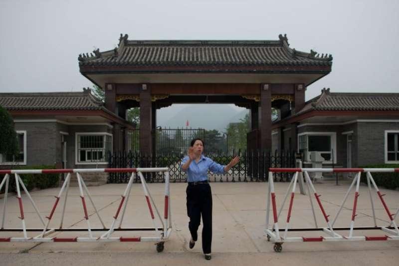 2013年9月12日,北京郊區秦城監獄入口處,一名女警員試圖阻止記者拍照。(美國之音)