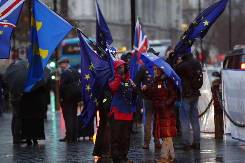 倫敦街頭仍有民眾揮舞著歐盟旗幟,希望英國能夠繼續留在歐盟。(美聯社)