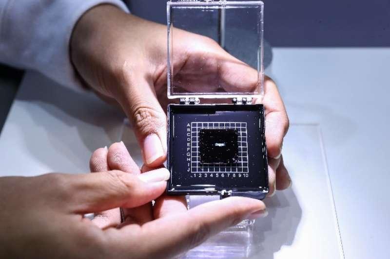 2018年10月8日,工作人員在全國雙創活動周媒體開放日上展示光子人工智慧晶片。(新華社)