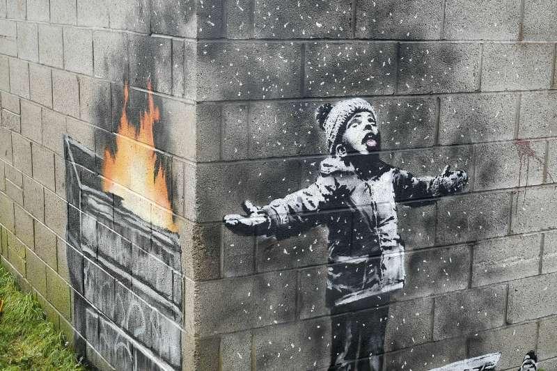 英國街頭塗鴉大師班克西(Banksy)的作品,接雪花/灰燼的男孩(AP)