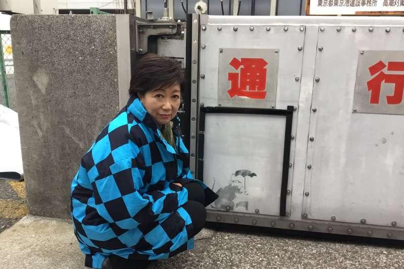 東京都一處防潮門有人塗鴉畫了小老鼠撐傘圖,被傳可能是英國知名塗鴉藝術家班克西的作品。東京都知事小池百合子在推特上傳她與小老鼠圖的合照。(小池百合子推特)
