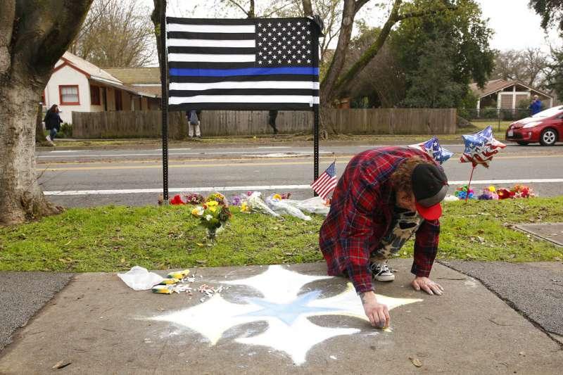 鎮上民眾自備象徵執法人員的藍色條紋旗,向殉職的女警致意。(美聯社)