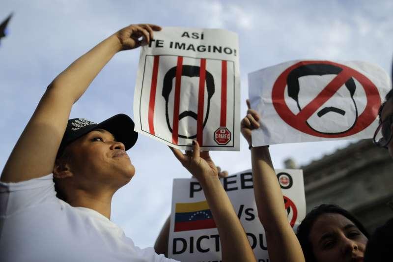 阿根廷的委內瑞拉移民,高舉反馬杜洛的標語,要求馬杜洛下台。(美聯社)