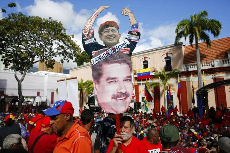 支持馬杜洛的民眾穿著紅衫在總統府前示威,高舉查維茲與馬杜洛的頭像。(美聯社)