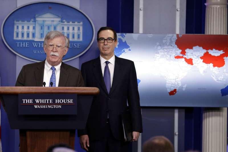 白宮國家安全顧問波頓與財政部長馬努欽在白宮舉行記者會,說明美國對委內瑞拉的經濟制裁。背後的世界地圖卻透露玄機。(美聯社)