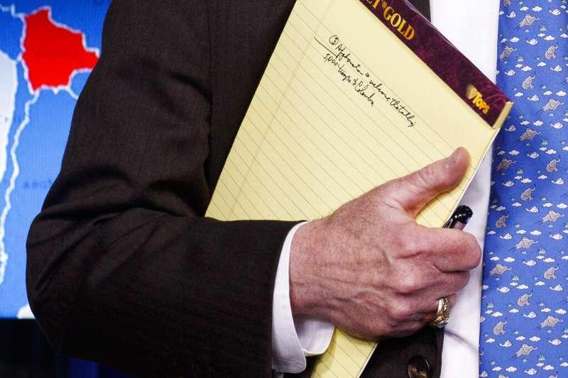 白宮國安顧問波頓在白宮召開記者會,說明對委內瑞拉的制裁,被眼尖媒體拍到手上筆記寫著「派兵5千赴哥倫比亞」。(美聯社)