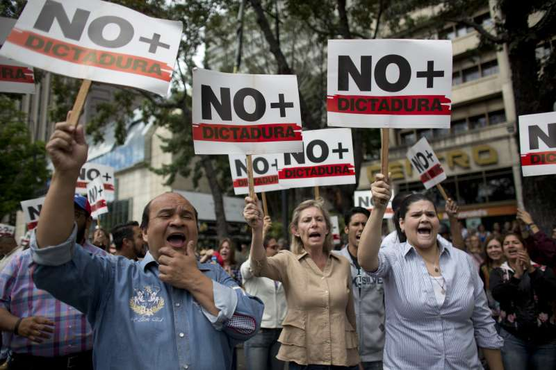 卡拉卡斯罷工遊行,民眾手舉「拒絕獨裁」標語。(美聯社)