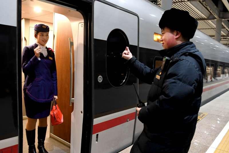 2019年1月22日,G402次列車停靠在新鄉東站,列車餐吧長鄒小娟在車門處接過丈夫李翔的餐包後互相做出「比心」的手勢。李翔是新鄉東站工作人員,小小的保溫餐包傳遞著小倆口甜蜜的愛情。(新華社)