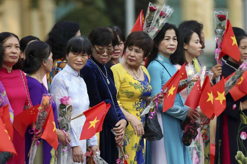 2017年11月12日,穿著越南傳統服飾手拿五星旗的民眾在街頭歡迎朱國國家主席習近平到河內訪問。(AP)