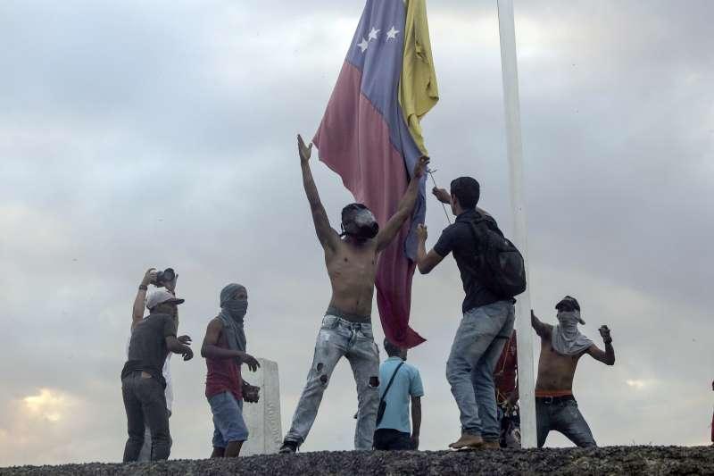 反馬杜洛的民眾在巴西和委內瑞拉邊境示威,拆下委內瑞拉的國旗。(AP)
