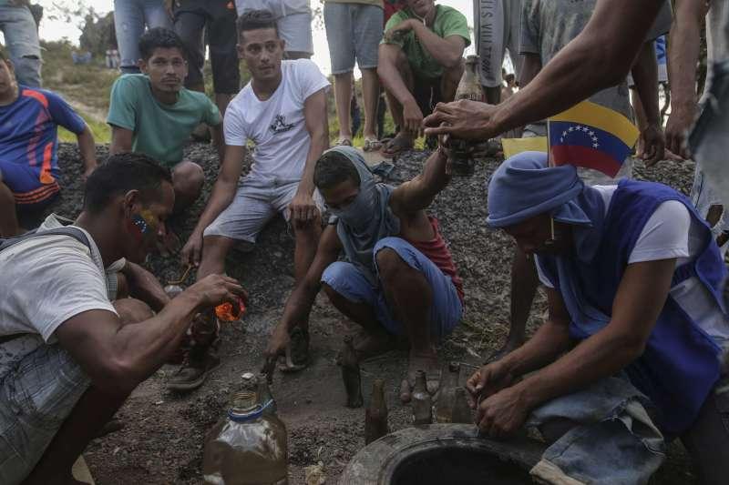 反馬杜洛的民眾在委內瑞拉和巴西邊境製作汽油彈,準備用來反擊軍方的攻擊。(AP)