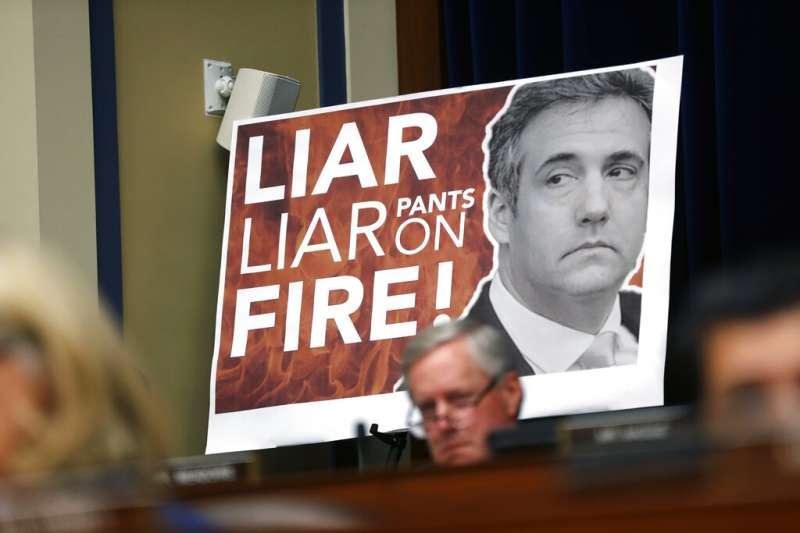 川普御用律師柯恩在國會作證,場邊出現「騙子、騙子、開除!」的海報。(美聯社)