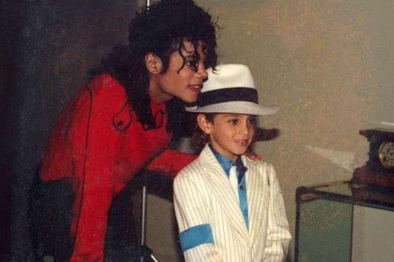 1990年代羅布森小的時候和麥可傑克森在一起。(BBC中文網)