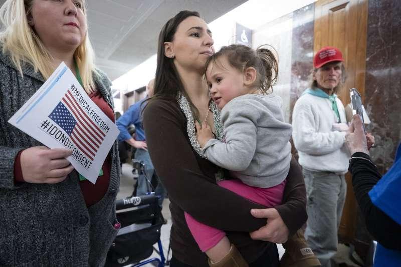 美國母親抱著孩童參加反對疫苗的集會活動。(AP)