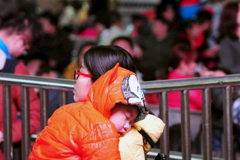 一名中國婦女帶著小孩在春運時期的火車站等待上車。(美國之音)