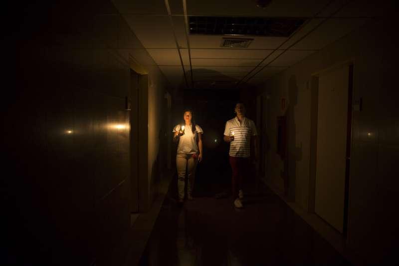 2019年3月7日,委內瑞拉首都卡拉卡斯的一家醫院內,醫護人員只能靠著蠟燭照明。(美聯社)