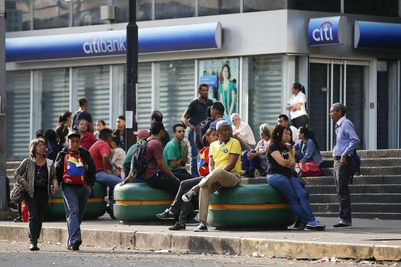 2019年3月8日,委內瑞拉地鐵因為停電停駛,民眾在街上等待接駁公車。(美聯社)