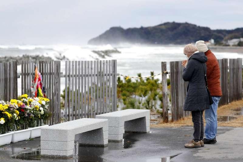 311日本大地震罹難者的遺族11日在海邊悼念逝去的親友。(美聯社)