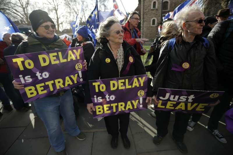 2019年3月14日,支持脫歐的英國民眾在國會外高舉「推遲就是背叛」的標語。(美聯社)