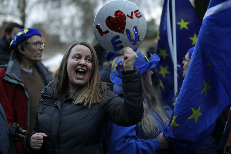 2019年3月14日,支持留歐的英國民眾在國會外舉著「我愛歐盟」。(美聯社)