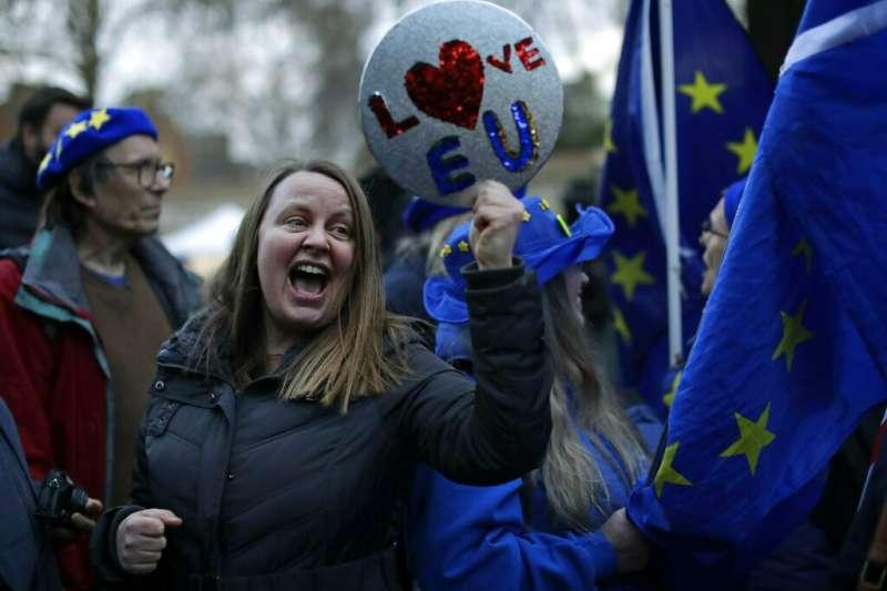 反對脫歐的英國民眾在街頭示威,舉著「愛歐盟」的標語牌。(美聯社)