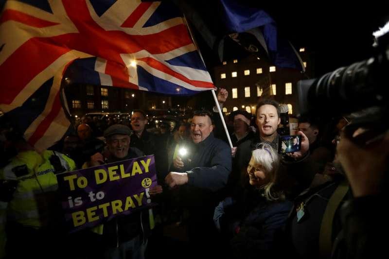 反對推遲脫歐的英國民眾在倫敦街頭揮舞英國國旗,高舉標語:推遲就是背叛!(美聯社)