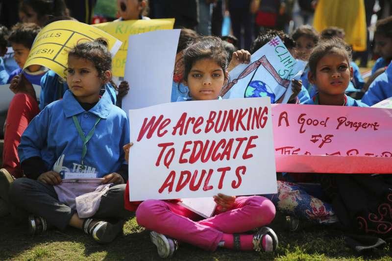 印度少女手持「我翹課是為了教育成人」的標語。(AP)
