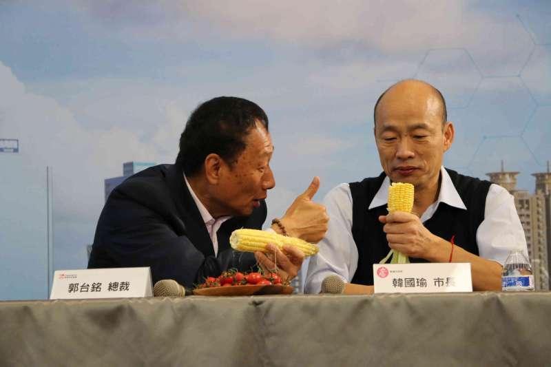 鴻海集團總裁郭台銘(左)將自家永齡農場生產的玉米,分送高雄市長韓國瑜(右)等貴賓食用,兩人當場啃起玉米。(高市府提供)