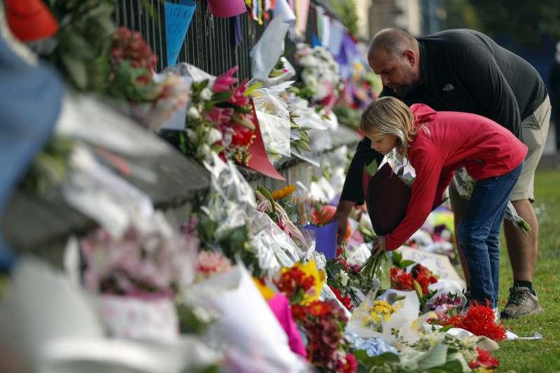 2019年3月16日,紐西蘭民眾到基督城植物園擺放鮮花,悼念恐攻案死者。(美聯社)