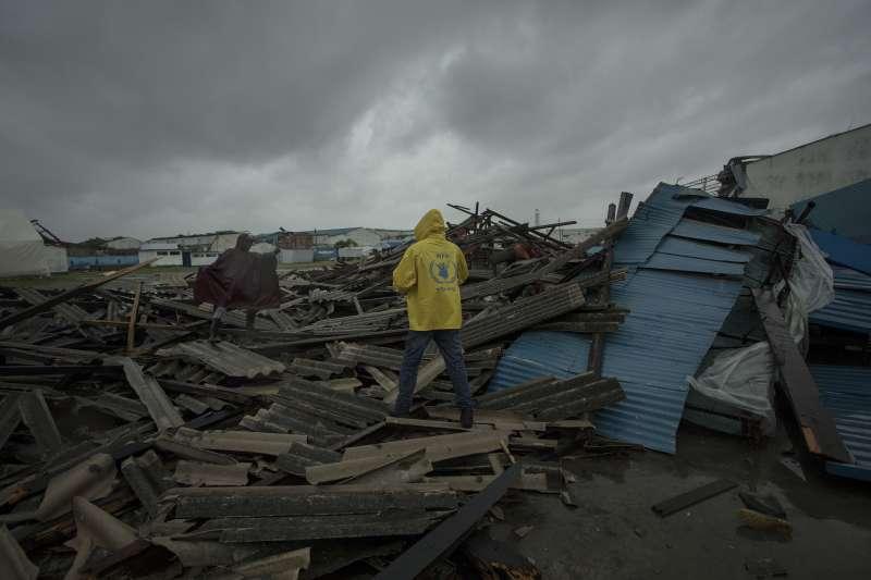 穿著黃背心的世界計畫糧食署(WFP)人員在貝拉視察災情。(美聯社)