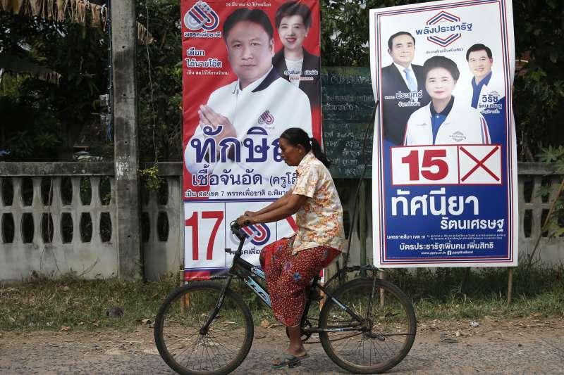 泰國東北部呵叻,一名婦女騎腳踏車經過候選人的宣傳海報。美國《彭博社》指出,泰國東北部與南部的窮苦橡膠農將成為牽動這次大選結果的關鍵族群(美聯社)