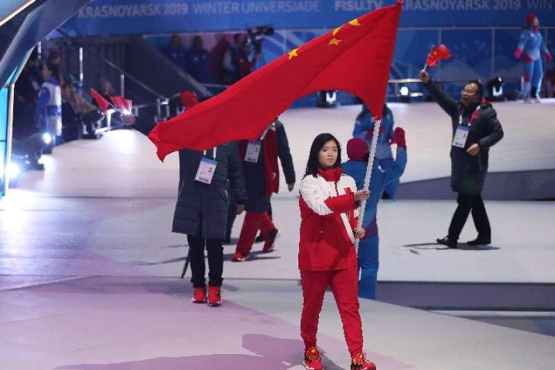 中國體育代表團旗手、單板滑雪運動員楊詩琦在開幕式上高舉國旗入場。(新華社)