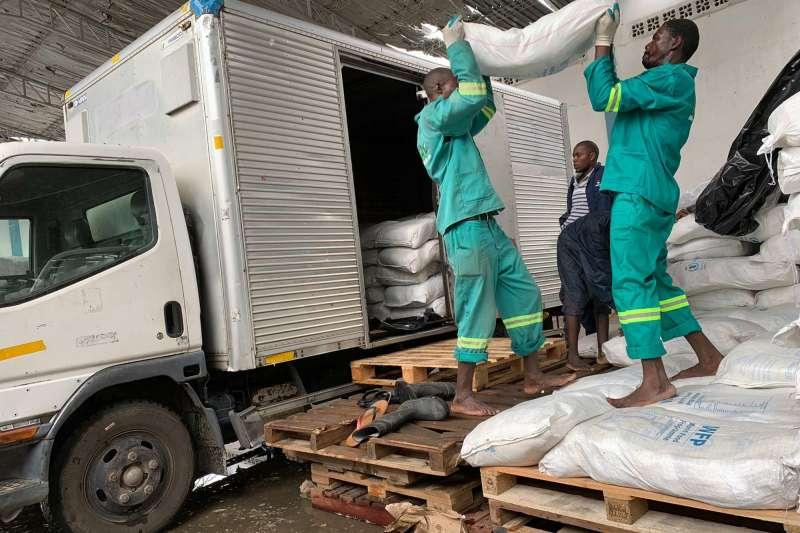 世界糧食計畫署(WFP)的工作人員正將數包麥片裝車。(AP)