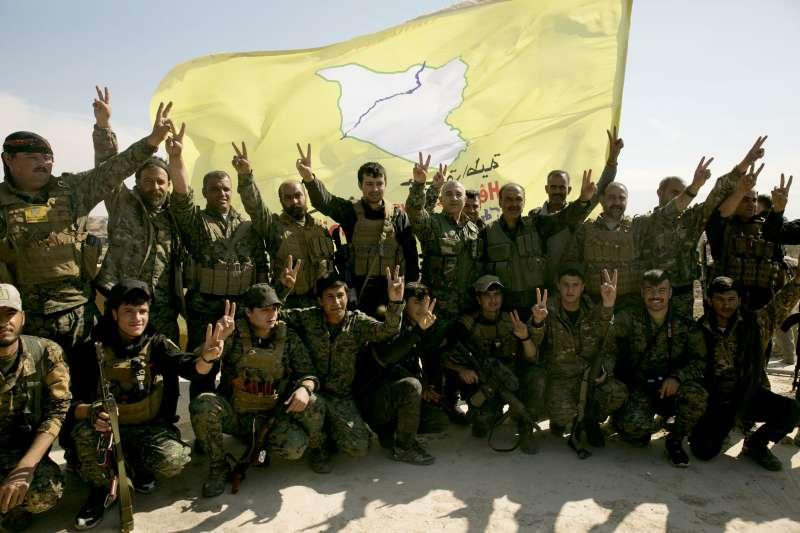 2019年3月23日,庫德族敘利亞民主軍在旗幟前合照,慶祝收復伊斯蘭國佔據地。(美聯社)