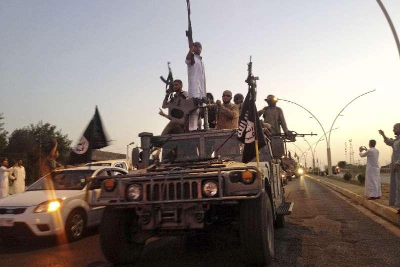 2014年6月23日,伊斯蘭國成員在伊拉克摩蘇爾遊行。(美聯社)