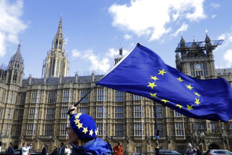 反脫歐的英國民眾24日在英國國會外揮舞歐盟旗幟。(美聯社)
