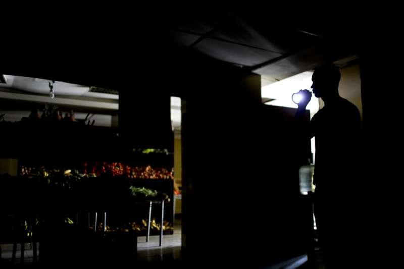 委內瑞拉再度陷入全國大停電,首都卡拉卡斯一間雜貨店的員工只能用手電筒在店裡做事。(美聯社)