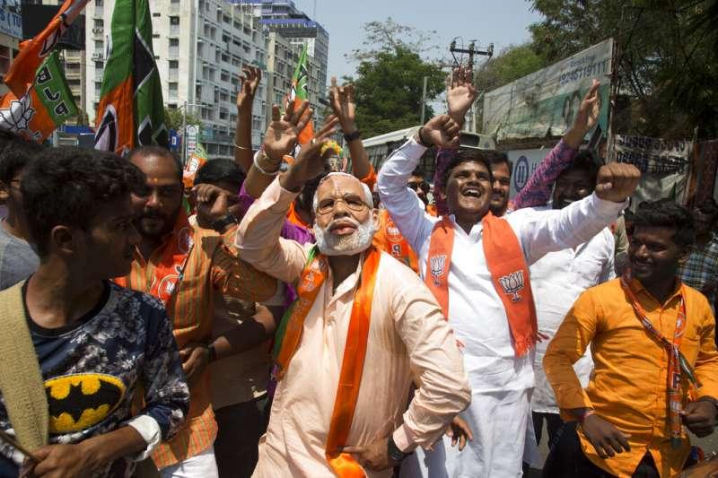 印度總理莫迪的支持者戴其面具跳舞。(AP)