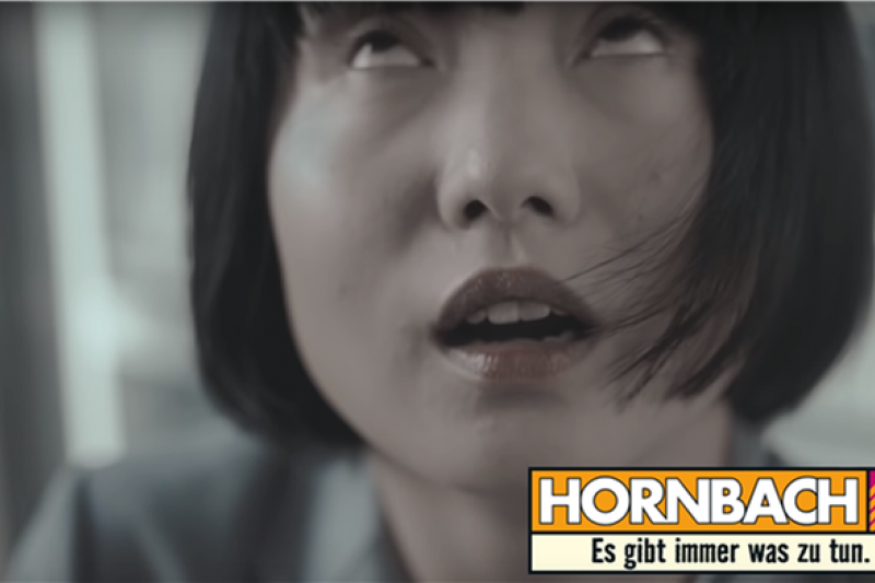 廣告中因聞到白人男性汗臭味表情扭曲的亞洲女性。(截自 YouTube)