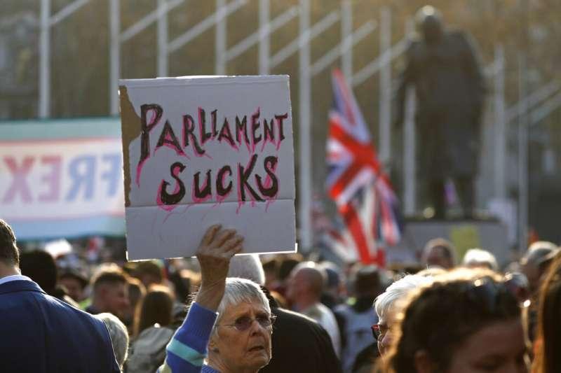 英國國會下議院29日針對首相梅伊的《退出協議》進行表決,場外憤怒的脫歐派民眾舉牌抗議。(AP)