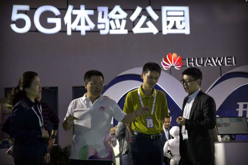 參觀者2018年9月26日在北京舉行的PT展覽上觀看中國科技公司華為的5G無線技術展示。(AP)