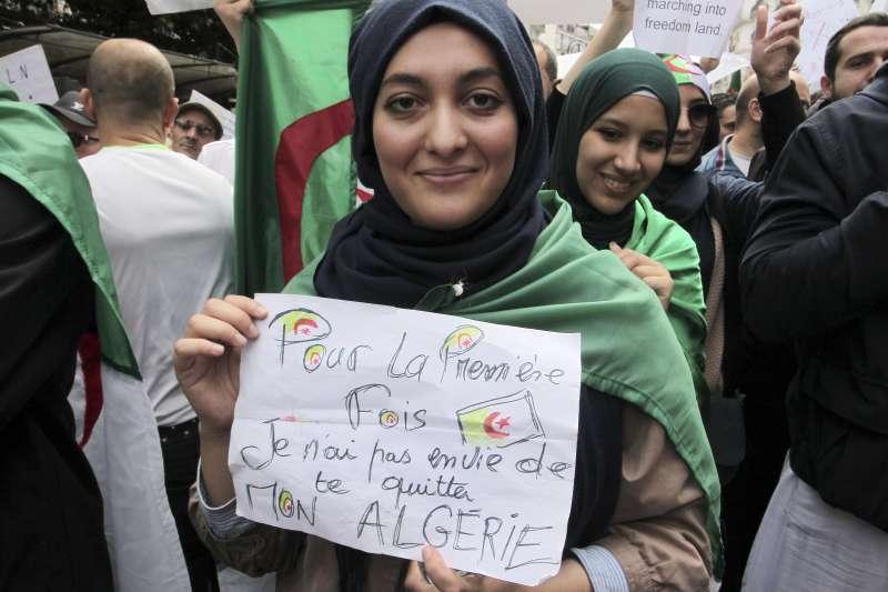 2019年2月至4月,阿爾及利亞爆發反政府示威,要求總統下台。這位女士手上的海報寫著:「有生以來,我第一次不想離開阿爾及利亞」(AP)