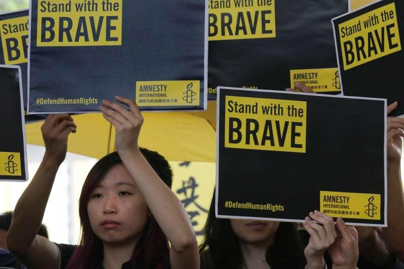 香港的佔領中環案9日上午宣判,運動發起人戴耀廷、陳健民、朱耀明等9人皆被認定觸犯煽惑他人犯公眾妨擾等罪,聲援者在法院外舉牌示威。(美聯社)